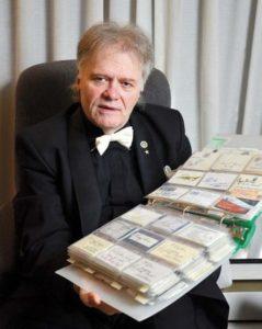 uomo con in mano centinaia di biglietti da visita