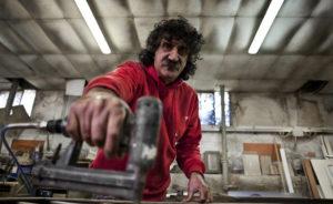 Metalmeccanico che mentre inchioda una lamiera guarda dentro l'obbiettivo